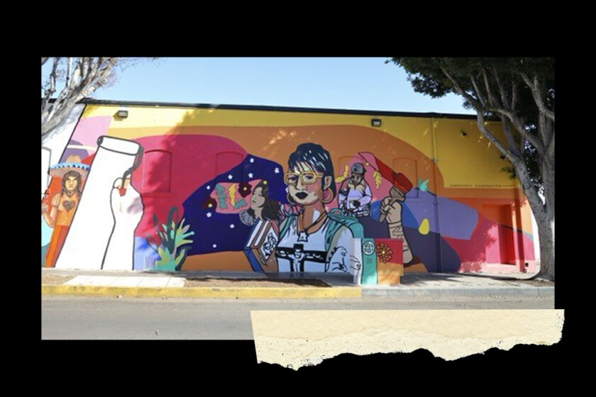 A brightly colored mural on the side of a building is seen from the street.