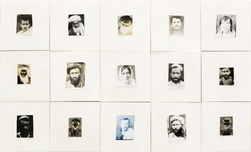 ردیف عکس هایی که در حصیرهای بزرگ سفید رنگ شده اند چهره های خسته شهروندان افغان را در طول جنگ نشان می دهد