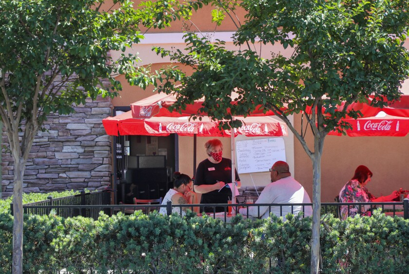 In one of the outdoor dining areas at J&M Family Restaurant waitress Kimberly Forrest takes customer's order.