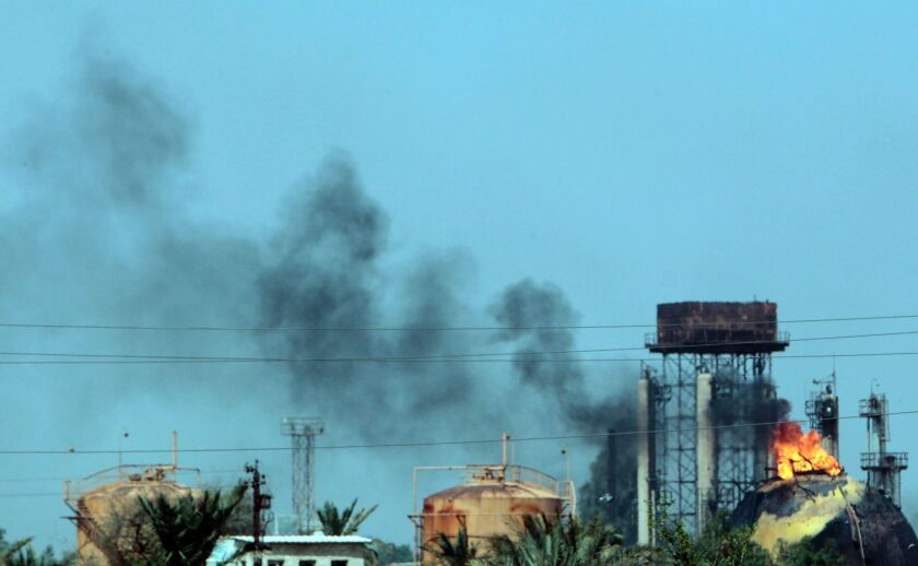 Flames and smoke rise from tanks after a militant attack on the Taji natural gas plant.