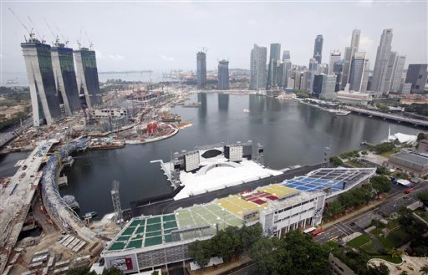 The Marina Bay Sands construction site, left, faces Singapore's financial skyline on Wednesday July 8, 2009, in Singapore. Las Vegas Sands Chairman Sheldon Adelson said Wednesday, the opening of the company's US$5.5 billion Singapore casino and resort will be delayed until early next year because of problems sourcing construction materials. (AP Photo/Wong Maye-E)