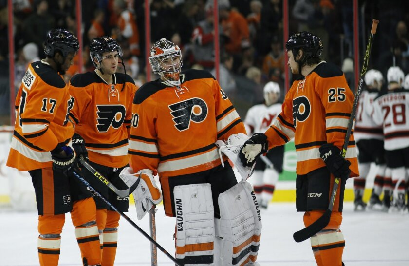 Philadelphia Flyers' Ryan White (25) meets with Michal Neuvirth (30), Brandon Manning (23) and Wayne Simmonds (17) after losing an NHL hockey game, 2-1, in overtime to the New Jersey Devils, Saturday, Feb. 13, 2016, in Philadelphia. (AP Photo/Matt Slocum)