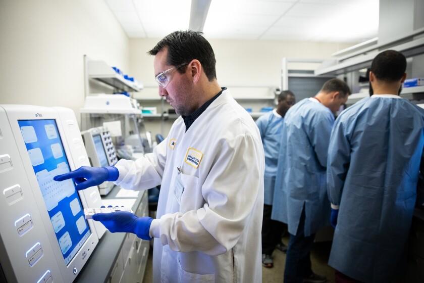 Un técnico de la UC Davis carga una muestra en el analizador ePlex de GenMark Diagnostics.