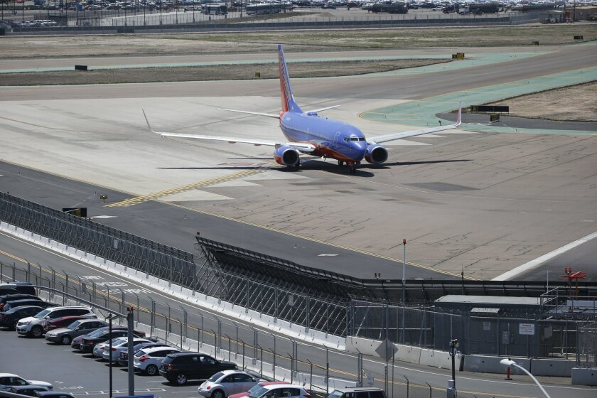In this Friday, May 13, 2016, photo, as a commercial airliner taxis for takeoff, the perimeter fencing and razor wires show the layers of security at San Diego International Airport. An Associated Press investigation has documented perimeter breaches at many of the busiest airports in the U.S. (AP