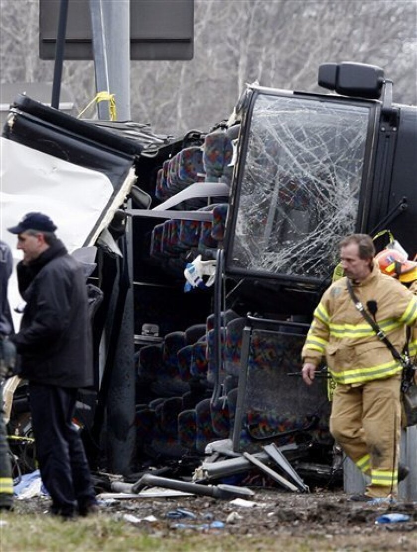 FILE - This March 12, 2011 file photo shows emergency personnel investigating the scene of a bus crash on Interstate-95 in the Bronx borough of New York. The driver of the tour bus that crashed while returning from a quick overnight trip to a casino, killing 15, has been indicted on manslaughter charges, a law enforcement official said Thursday, Sept. 1, 2011. (AP Photo/David Karp, file)