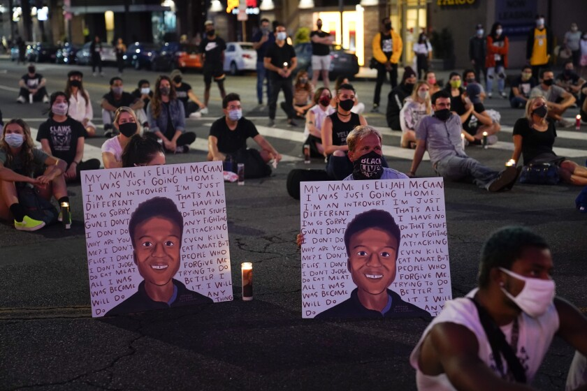 Two people hold posters showing images depicting Elijah McClain