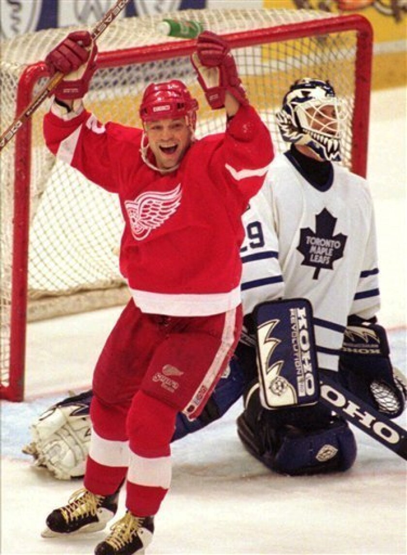 FILE - This March 19, 1996, file photo shows Detroit Red Wings' Dino Ciccarelli, left, celebrating a third-period goal by teammate Sergei Fedorov as Toronto Maple Leafs goalie Felix Potvin, right, looks to the scoreboard at Joe Louis Arena in Detroit. Ciccarelli, Cammi Granato and Angela James were elected to Hockey Hall of Fame, Tuesday June 22, 2010.(AP Photo/Tom Pidgeon, File)