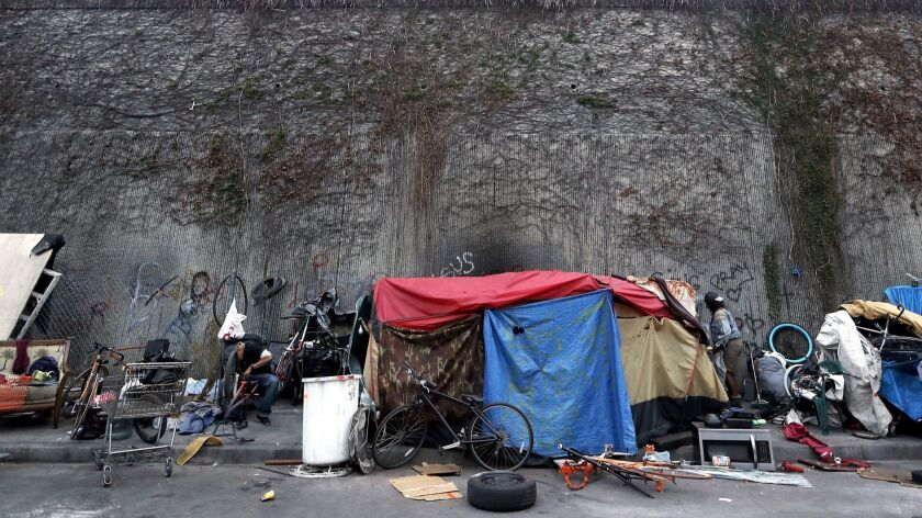 LOS ANGELES, CALIF. - MAY 22, 2018. Homeless people live in tents beside a wall that seperates Gra