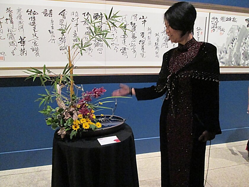 La Jollan Jackie Zhang, master teacher at Ohara Ikebana, with her floral piece inspired by Pan Gongkai's wall-length 'Noble Virtues.' Lonnie Hewitt