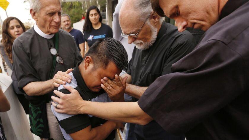 El solicitante de asilo guatemalteco Hermelindo Che Coc, de 31 años, con el padre Tom Carey, el reverendo David Farley y el reverendo Matthias Peterson-Brandt, de izquierda a derecha, rezan frente al edificio federal de Los Ángeles, antes de una audiencia (Al Seib / Los Angeles Times).