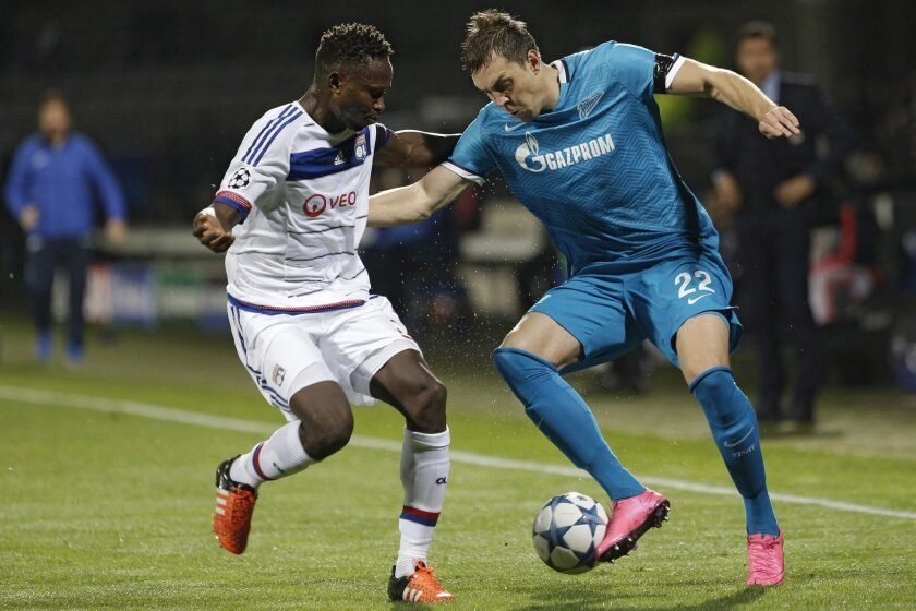 Lyon's Mapou Yanga-Mbiwa, left, challenges for the ball with Zenit St Petersbourg's Artem Dzyuba during the Champions League Group H soccer match between Lyon and Zenit St Petersburg at the Gerland stadium in Lyon, central France, Wednesday, Nov. 4, 2015. (AP Photo/Laurent Cipriani)