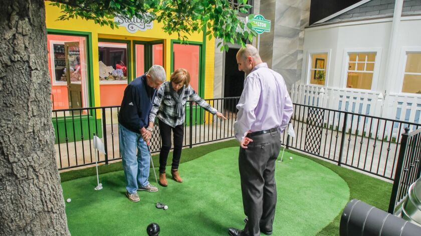 Glenner Town Square founder Scott Tarde, right, watches Bonita resident Sue Foley guides her husband, Bill, on the putting green. Glenner Town Square, a miniature memory village for Alzheimer's patients like Bill, will soon open inside a Chula Vista industrial building.