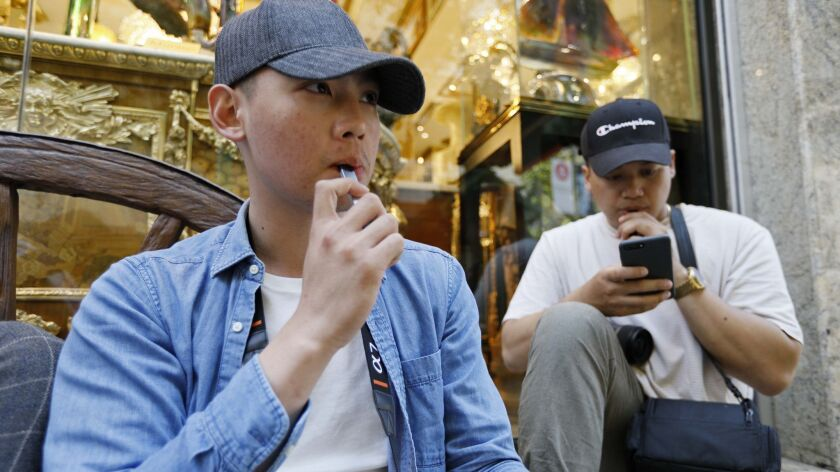 In this Monday, June 17, 2019, photo, Joshua Ni, 24, and Fritz Ramirez, 23, vape from electronic cig