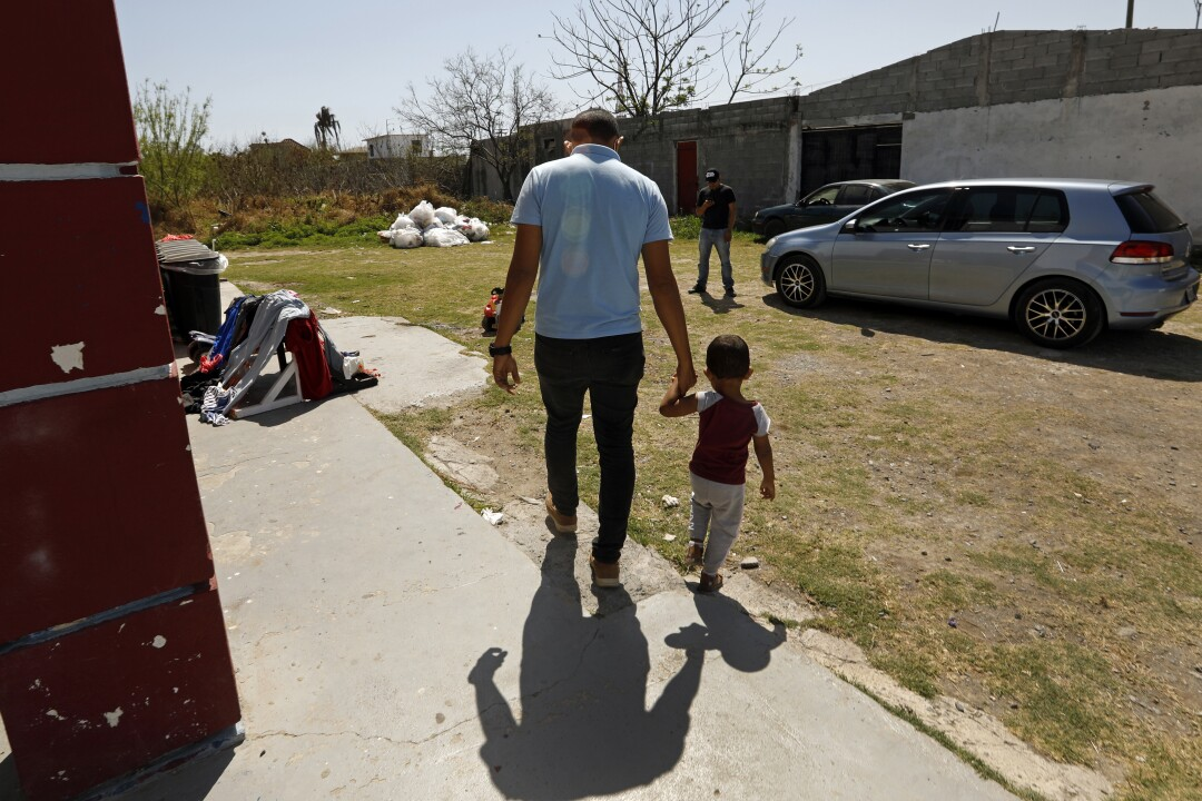 A man and his son, 2, walk outside a shelter.