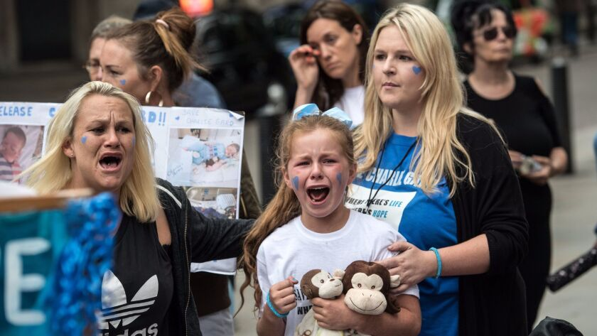 Demonstrators react to news that Charlie Gard's parents have withdrawn their application to bring th
