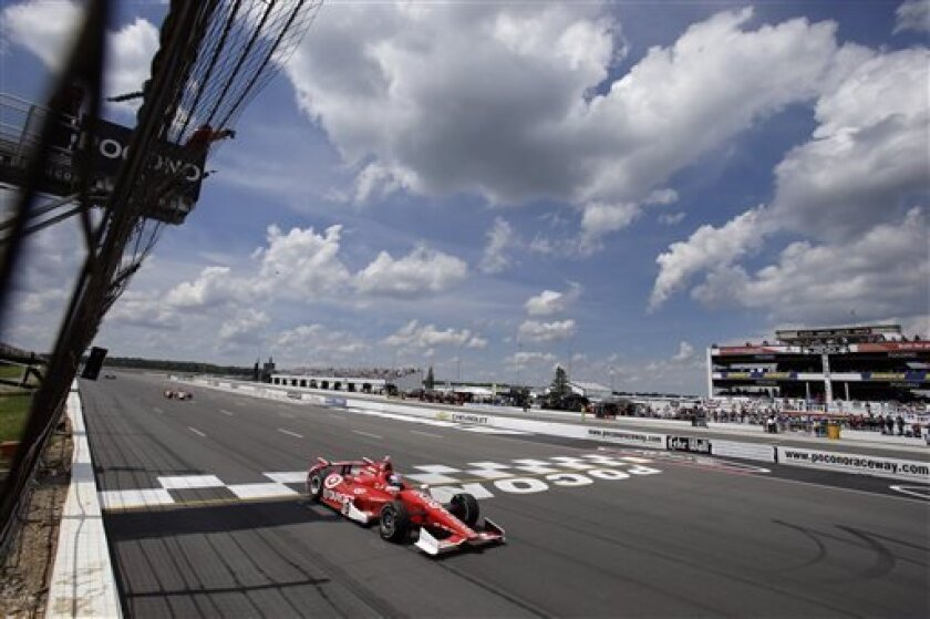 Scott Dixon, of New Zealand, takes the checkered flag to win the Pocono IndyCar 400 auto race, Sunday, July 7, 2013, in Long Pond, Pa. (AP Photo/Mel Evans)