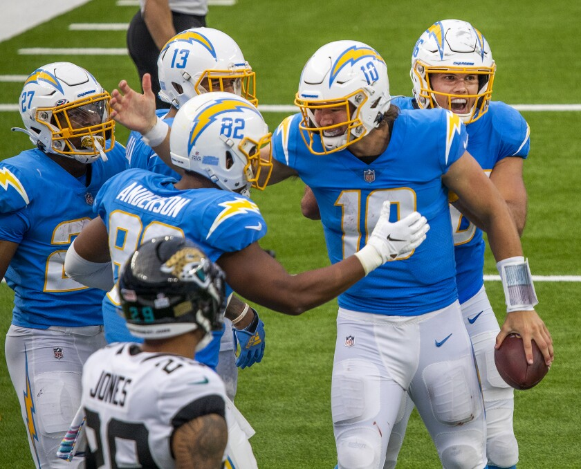 Chargers quarterback Justin Herbert is congratulated by teammates after his five-yard run for a touchdown.