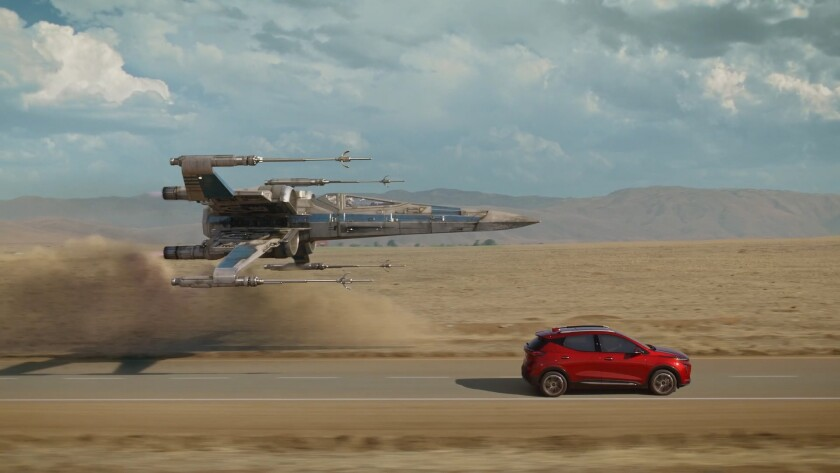"An X-wing from the ""Star Wars"" universe flies alongside a Bolt EUV in Chevrolet's ""Magic is Electric"" ad."