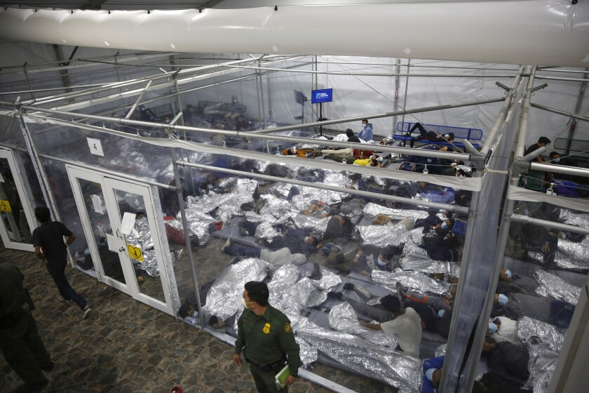 FILE - In this March 30, 2021, file photo, minors are shown inside a pod at the Donna Department of Homeland Security holding facility, the main detention center for unaccompanied children in the Rio Grande Valley run by U.S. Customs and Border Protection (CBP), in Donna, Texas. A federal volunteer at the Biden administration's largest shelter for unaccompanied immigrant children says paramedics were called regularly during her the two weeks she worked there. She said panic attacks would occur often after some of the children were taken away to be reunited with their families, dashing the hopes of those left behind. The conditions described by the volunteer highlight the stress of children who cross the U.S.-Mexico border alone and now find themselves held at unlicensed mass-scale facilities waiting to reunite with relatives. (AP Photo/Dario Lopez-Mills, Pool,File)