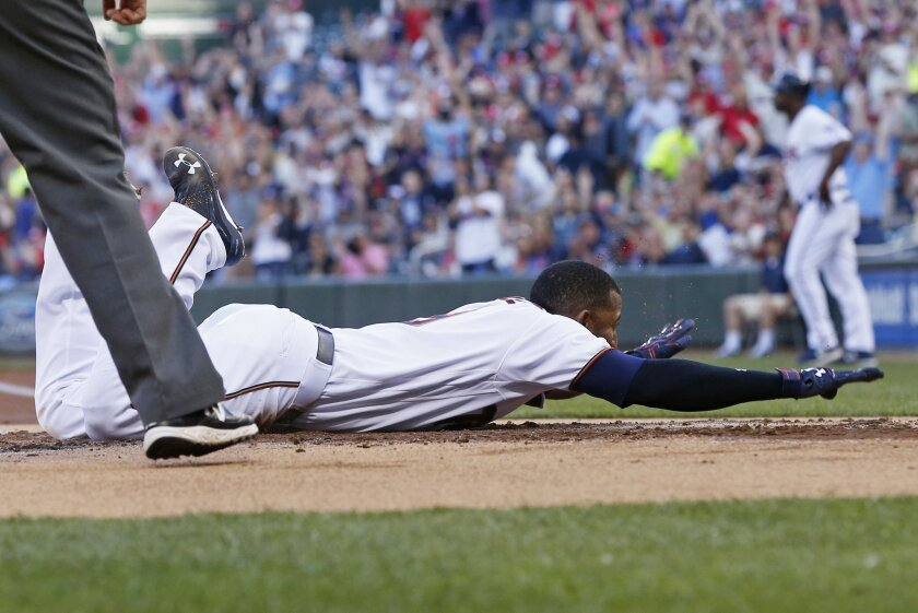 Minnesota Twins' Eduardo Nunez slides safely into home to score on an inside-the-park home run off Tampa Bay Rays pitcher Matt Moore during the first inning of a baseball game Thursday, June 2, 2016, in Minneapolis. (AP Photo/Jim Mone)