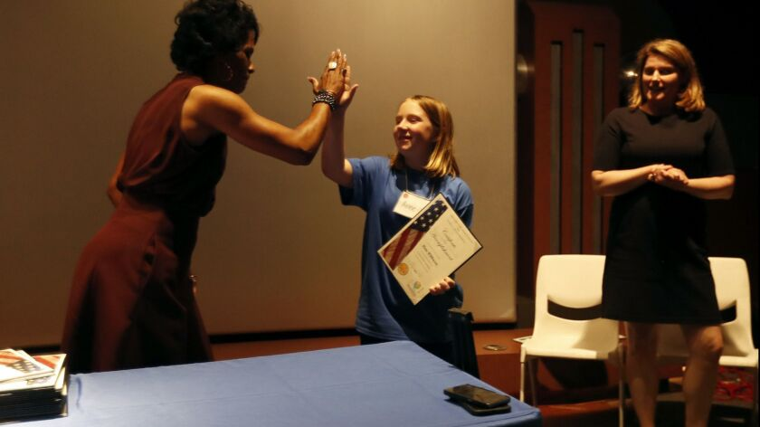 Annie Wilkinson, center, high fives Voviette Morgan, left, a special agent in charge of the criminal