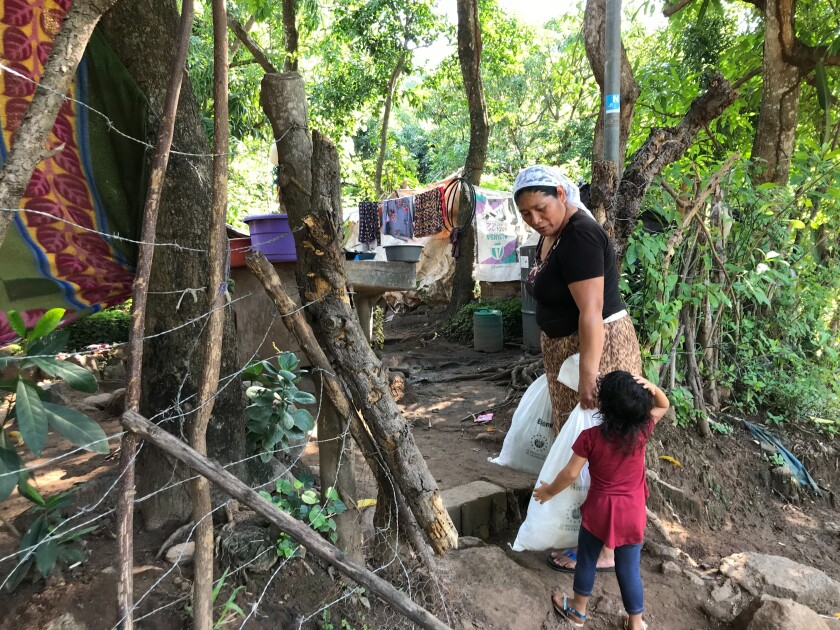 A woman carries packages of food aid while looking down at a child while surrounded by trees.