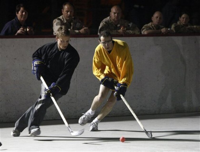 """Military personnel watch a hockey player of the CGHA (Canadian Forces Helicopter Afghanistan), left, playing against a member of the FAF (French Air Force) in a concrete-floored rink during Kandahar Ball Hockey League the at the """"Boardwalk"""" entertainment area of the Kandahar military base in Afghanistan, Wednesday, Feb. 3, 2010. Two dozen teams, mostly Canadian military servicemen, play a ball league to satisfy their love of ice hockey.(AP Photo/Pier Paolo Cito)"""