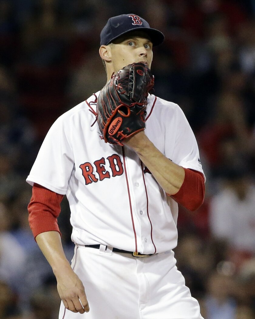 Boston Red Sox starting pitcher Clay Buchholz reacts after giving up a two-run home run to Colorado Rockies' Dustin Garneau during the fifth inning of a baseball game at Fenway Park, Thursday, May 26, 2016, in Boston. (AP Photo/Elise Amendola)