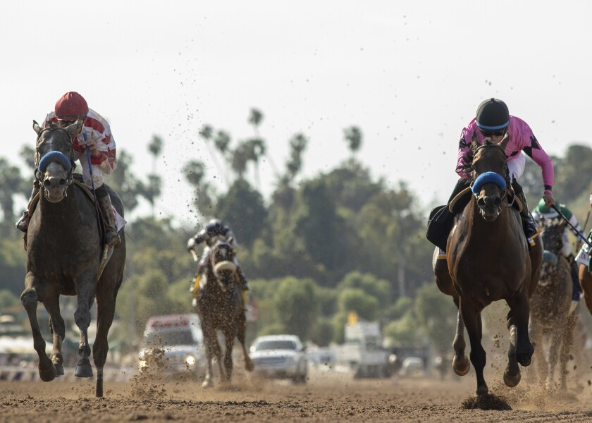 Roadster and jockey Mike Smith, left, catch Game Winner and Joel Rosario on Saturday to win the Santa Anita Derby in Arcadia.