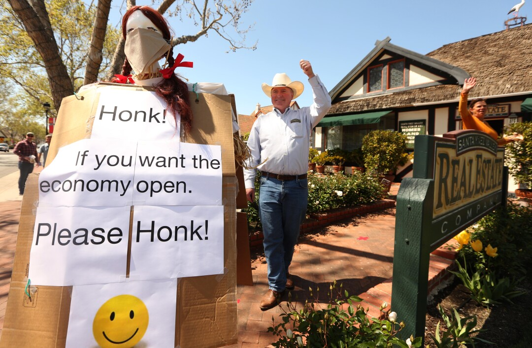 Realtor Allan Jones and his wife acknowledge a honking car last week while standing next to a sign he erected at his real estate office in Solvang in hopes the economy opens up again.