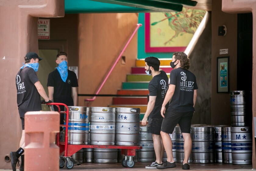 Employees at El Prez move kegs in Pacific Beach ahead of Memorial Day Weekend on May 22, 2020 in San Diego, California. The bar and restaurant was shut down by the county on Friday after images circulated on social media showing a lack of social distancing at the establishment.