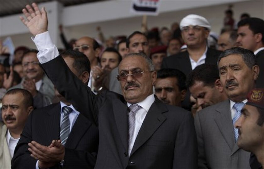 In this photo taken Friday, April 29, 2011, Yemeni President Ali Abdullah Saleh, center, waves to his supporters during a rally in Sanaa, Yemen. Yemeni President Ali Abdullah Saleh accepted an offer from the Saudi king to get medical treatment there for wounds from a rebel rocket attack, but had not yet left his country, officials close to the president said Saturday, June 4, 2011. (AP Photo/Muhammed Muheisen)