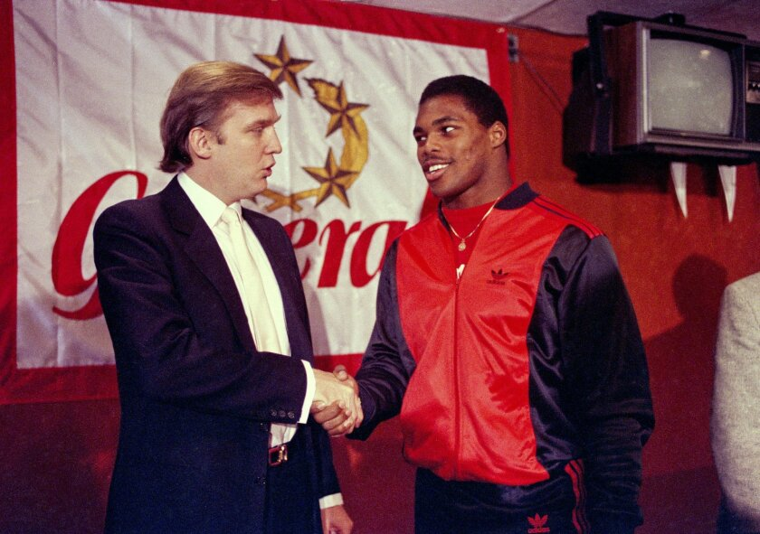 FILE - In this March 8, 1984, file photo, Donald Trump shakes hands with Herschel Walker in New York after agreement on a 4-year contract with the New Jersey Generals USFL football team. The New Jersey Generals have been largely forgotten, but Trump's ownership of the team was formative in his evol