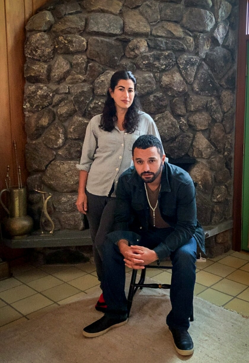 Jehane Noujaim, seated, and Karim Amer in a portrait in front of a fireplace.