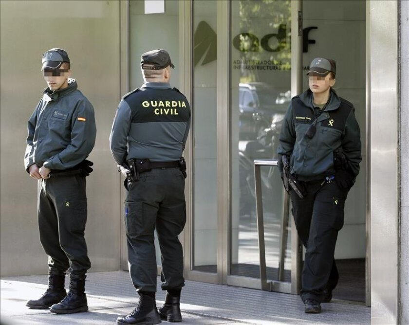 Civil Guard officers watch the entrance to the Madrid headquarters of Adif, the agency that manages infrastructure projects in Spain, as part of an investigation that led to the  arrests of nine people for alleged irregularities in the construction of the high-speed AVE train linking Madrid and Bar