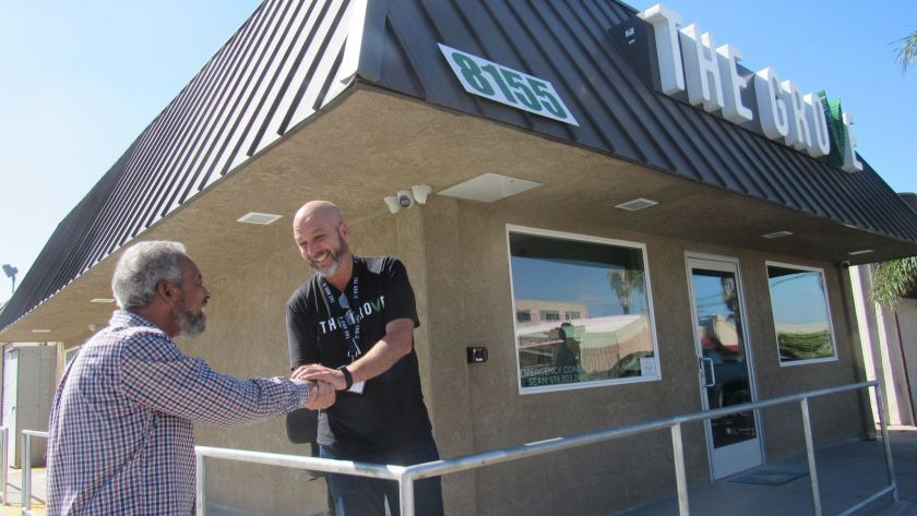 Ali Benson (left) shakes hands with Sean McDermott, the owner of La Mesa's lone medical marijuana dispensary, The Grove, in a photo taken last year. The city has clarified language in its Municipal Code so that people with a state-issued ID card will not be charged tax while those without the card will have to pay an additional 4 percent tax.