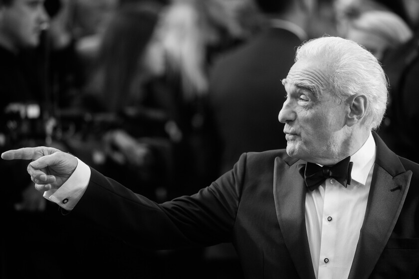 """The Irishman"" director Martin Scorsese, in a tux, looks and points at something offscreen."