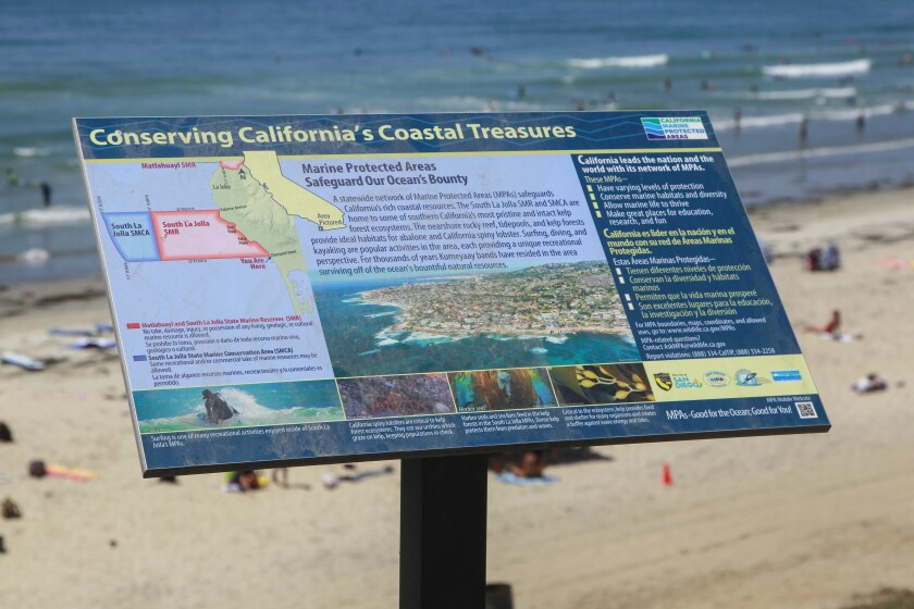 An interpretive sign at the foot of Diamond Street in Pacific Beach explaining the South La Jolla marine protected area (background) on August 9, 2019 in San Diego, California.