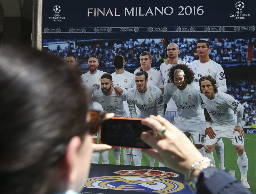 A man poses in a hole, giving his face to Real Madrid Brazilian defender Marcelo, on a billboard with a picture of the Real Madrid team, at the Champions Festival event, in Milan, Italy, Thursday, May 26, 2016. The Champions League soccer final between Real Madrid and Atletico Madrid will be held a