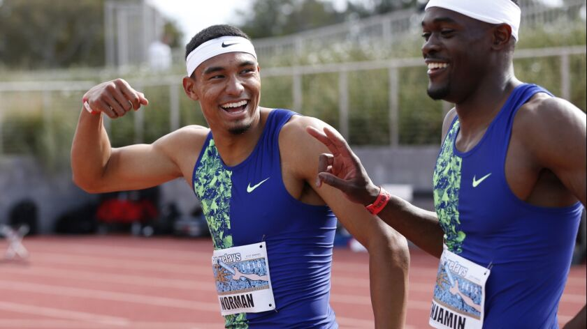 Michael Norman, left, and Rai Benjamin share a light moment after their epic 400-meter race at the Mt. SAC Relays on Saturday.