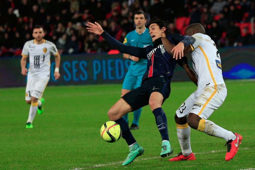PSG's Edinson Cavani, center, challenges for the ball with Lille's Adama Soumaoro, during their League One soccer match, at the Parc des Princes stadium, in Paris, Saturday, Feb. 13, 2016. (AP Photo/Thibault Camus)