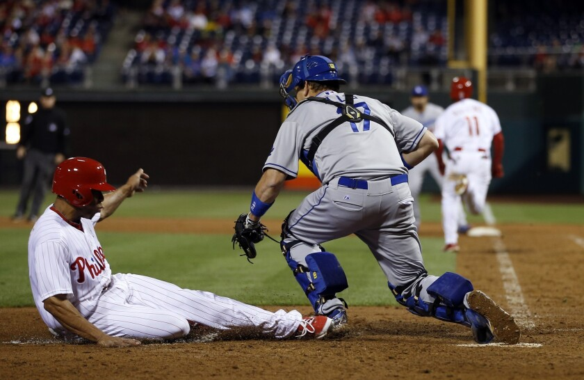 Dodgers catcher A.J. Ellis makes the catch to force out Phillies center fielder Ben Revere in the seventh inning Friday night.