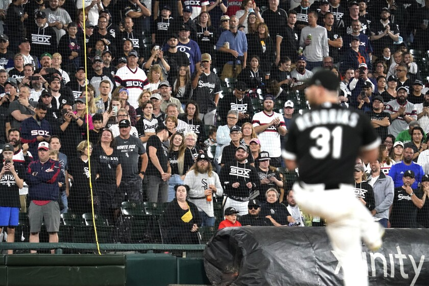 FILE - In this Saturday, Oct. 2, 2021, file photo, fans stand as they watch Chicago White Sox relief pitcher Liam Hendriks work during the ninth inning of a baseball game against the Detroit Tigers in Chicago. The White Sox have a rare opportunity to capture the spotlight and expand their fan base in a city where they're often overshadowed by their neighbors a few miles north. They're in the playoffs for the second year in a row, a first for the charter American League franchise, after running away with the Central division. (AP Photo/Nam Y. Huh, File)