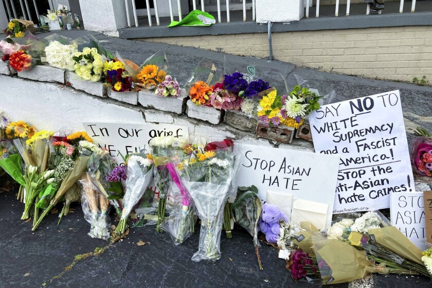 """Flowers and candles sit alongside signs, one of which says """"Stop Asian hate."""""""