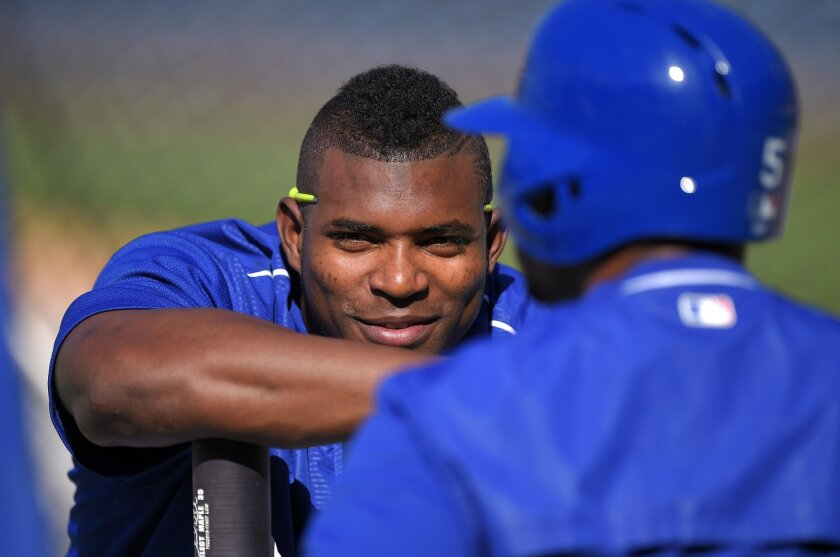The Dodgers' Yasiel Puig, left, talks with Alberto Callaspo prior to a game against the San Francisco Giants on Friday.