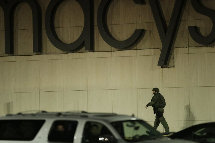 An official wearing tactical gear walks outside of the Garden State Plaza Mall following reports of a shooter, Monday, Nov. 4, 2013, in Paramus, N.J. Hundreds of law enforcement officers converged on the mall Monday night after witnesses said multiple shots were fired there. (AP Photo/Julio Cortez)