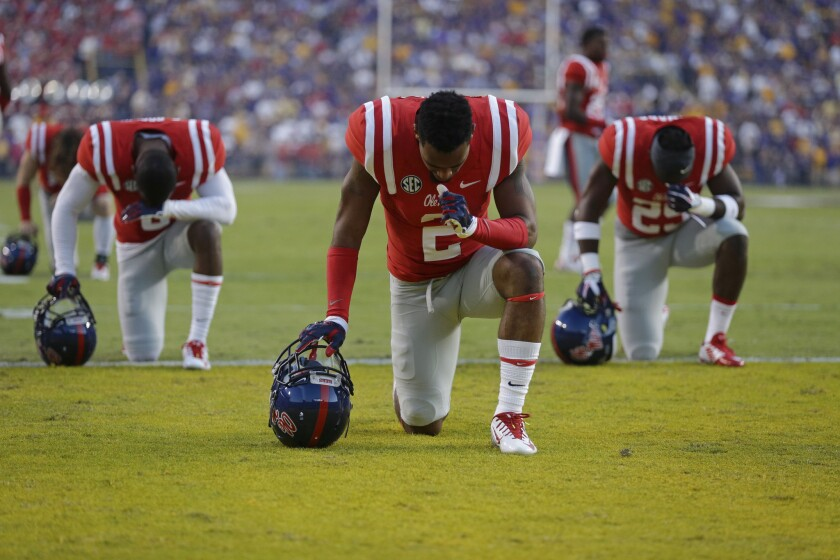 Mississippi players pray in the end zone before an NCAA college football game against LSU in Baton Rouge, La. in 2014. As football season begins, with it comes religion on the gridiron.