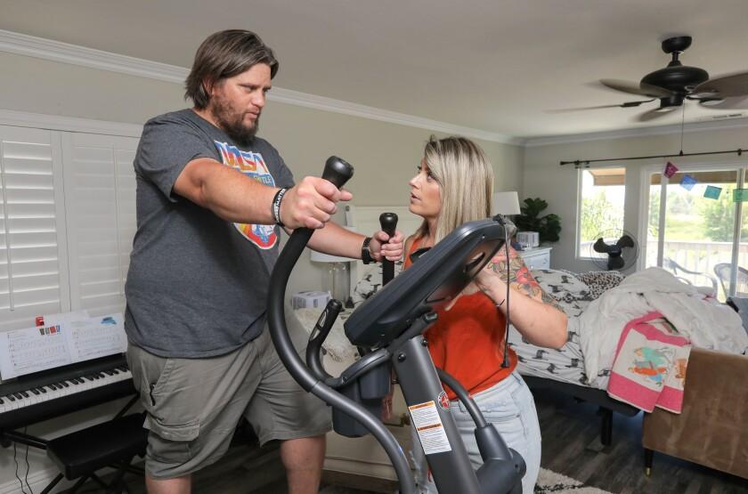 Nikki Stephens assists her husband John as he uses an exercise machine at their Murrieta home.