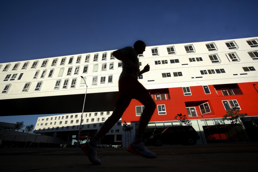 A jogger makes his way past the brand new One Santa Fe apartment building on Santa Fe Avenue in the Arts District section of Downtown Los Angeles.