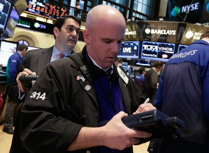 Traders Mark Muller, left, and Kevin Walsh work on the floor of the New York Stock Exchange Tuesday, Dec. 3, 2013. Stocks are opening lower on Wall Street as investors hold back ahead of economic reports that could influence when the Federal Reserve will start reducing its stimulus. (AP Photo/Richard Drew)